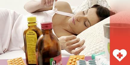 Frau liegt im Bett davor stehen Medikamente