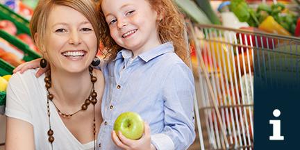 Frau mit Kind das einen Apfel hält