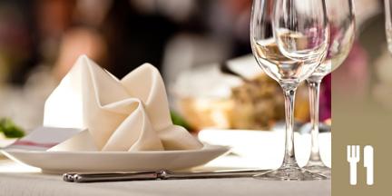 Teller mit Stoffserviette und Weingläser auf gedecktem Tisch