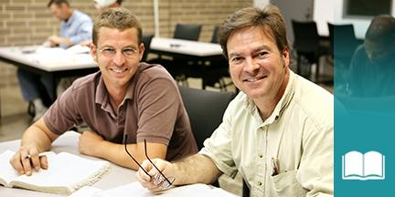 Zwei Männer sitzen an Schulbank