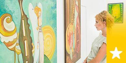 Frau betrachtet Bilder an Wand
