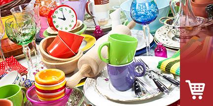 Vollgestellter Tisch mit Haushaltsutensilien und Geschirr