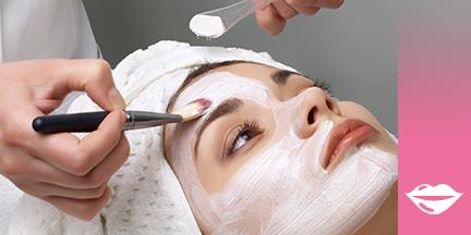 Frauenkopf Haare in Handtuch eingeschlagen Gesicht wird mit weißer Maske eingepinselt