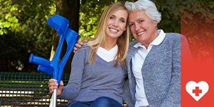 Alte Frau sitzt auf Bank und umarmt junge Frau die Krücken hält