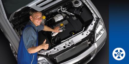Mechaniker vor geöffnetem Motorraum zeigt Daumen hoch
