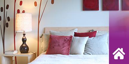 Bett mit Kissen daneben Nachttisch mit eingeschalteter Lampe