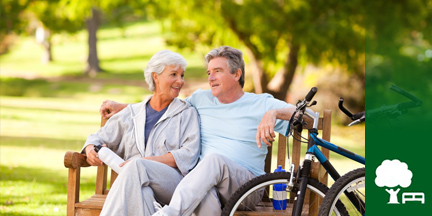 Älteres Paar auf Parkbank davor ein Fahrrad