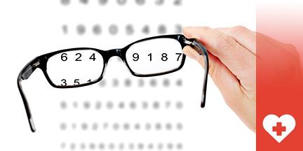 Hand hält Brille vor Sehtesttafel