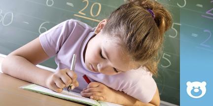 Mädchen sitzt vor Schultafel und schreibt in ein Heft
