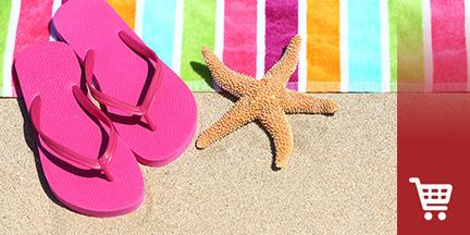 Buntes Badehandtuch mit pinken Flip Flops und Seestern auf Sand