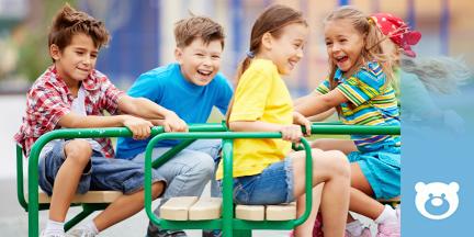 Kinder fahren Drehkarussell auf einem Spielplatz