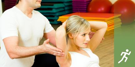 Frau macht Situps und wird dabei von einem Mann von hinten gestützt