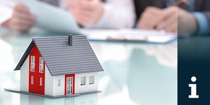 Miniatur eines Einfamilienhauses steht auf Tisch