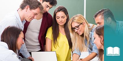 Gruppe von jungen erwachsenen Schülern steht um einen Bildschirm im Hintergrund Tafel