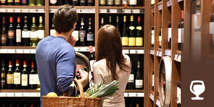 Paar mi Einkaufskorb vor Weinregal