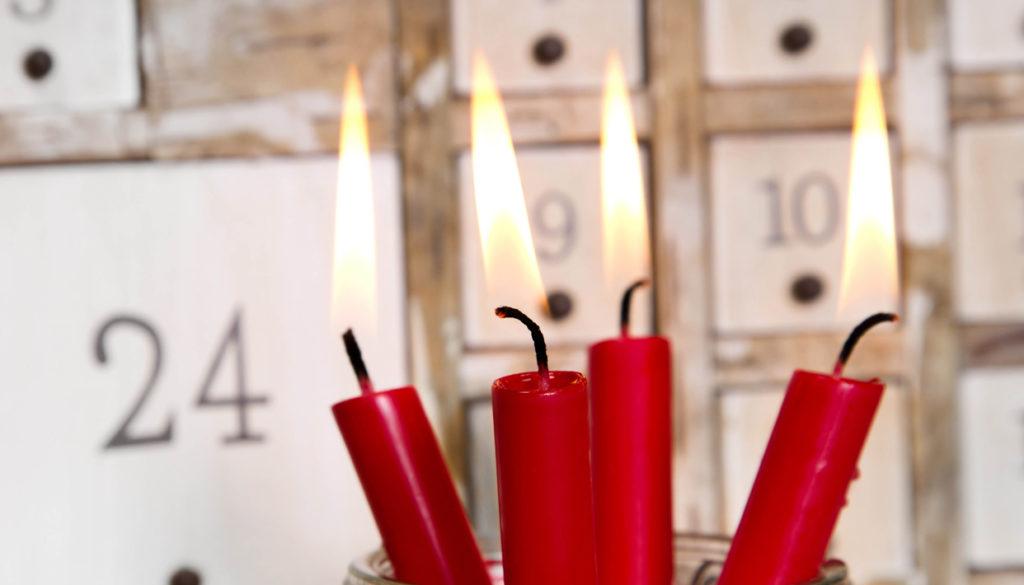 Vier rote brennende Adventskerzen mit Adventskalender