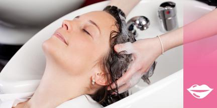 Einer Frau werden die Haare von Friseurin gewaschen