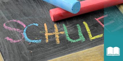 Tafel auf der mit bunter Kreide das Wort Schulde geschrieben steht