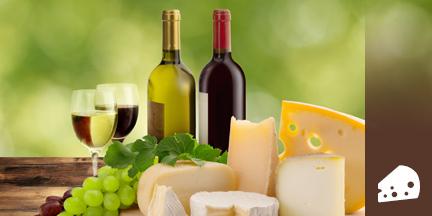 Käsestücke mit Trauben, Weinflaschen und Weingläsern