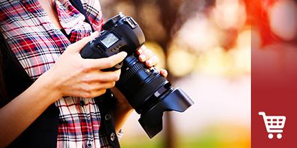 Frau hält Kamera mit großem Objektiv