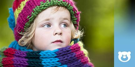 Kind mit buntem Schal und Mütze
