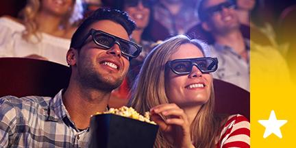 Paar mit 3D Brillen und Popcorn im Kino