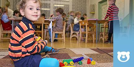 Spielendes Kind auf Teppich im Hintergrund sitzen Kinder an Tischen