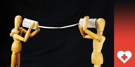 Zwei Holzgliederpuppen halten Dosentelefon