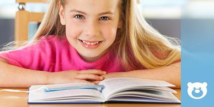 Mädchen sitzt vor aufgeschlagenem Buch