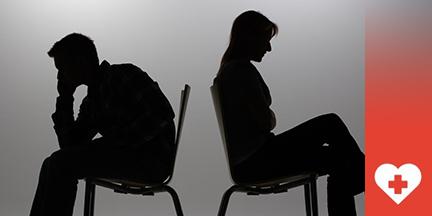 Silouette von Mann und Frau die Rücken an Rücken sitzen