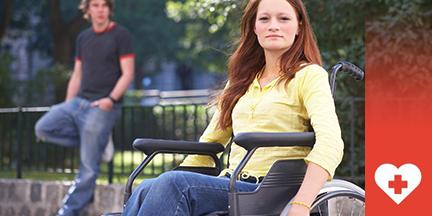 Junge Frau sitzt in Rollstuhl, im Hintergrund junger Mann