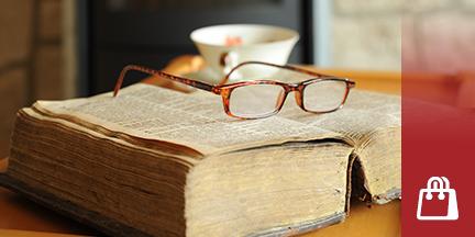 Auf altem aufgeschlagenen Buch liegt Lesebrille im Hintergrund Teetasse