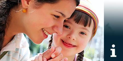 Junge Frau hält Hand von Mädchen mit Down-Syndrom