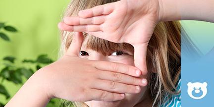 Kind formt ein Fenster mit den Händen und schaut hindurch