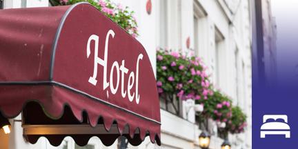 Rote Markise mit Aufschrift Hotel und im Hintergrund Hausfassade mit Blumenkästen